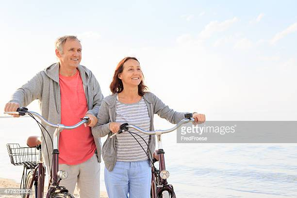 Mature couple outdoors walking on the beach