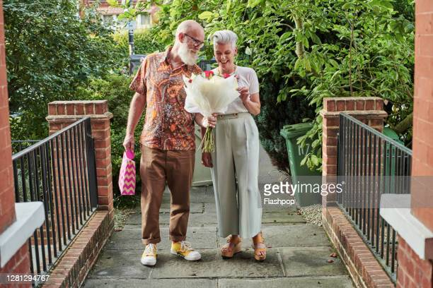 mature couple outside walking and carrying gifts and flowers - {{relatedsearchurl(carousel.phrase)}} stock pictures, royalty-free photos & images