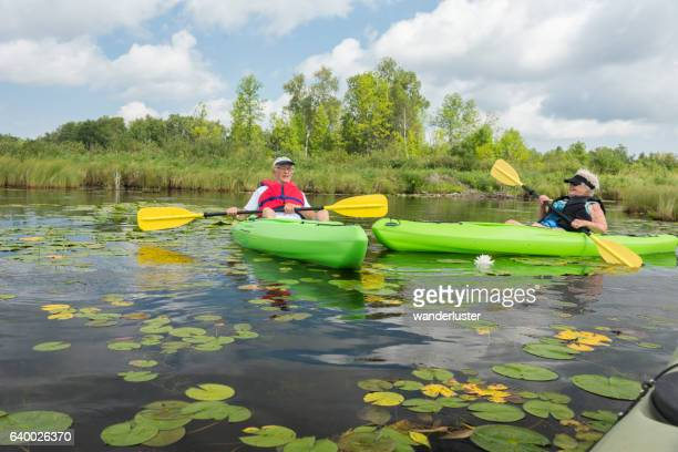 Mature couple paddles past lilypads