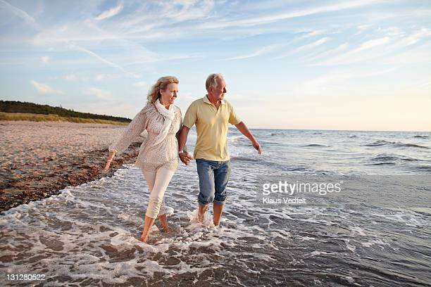 Mature couple paddling in sea looking at sunset