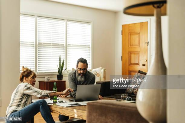 mature couple paying bills at home - husband stock pictures, royalty-free photos & images