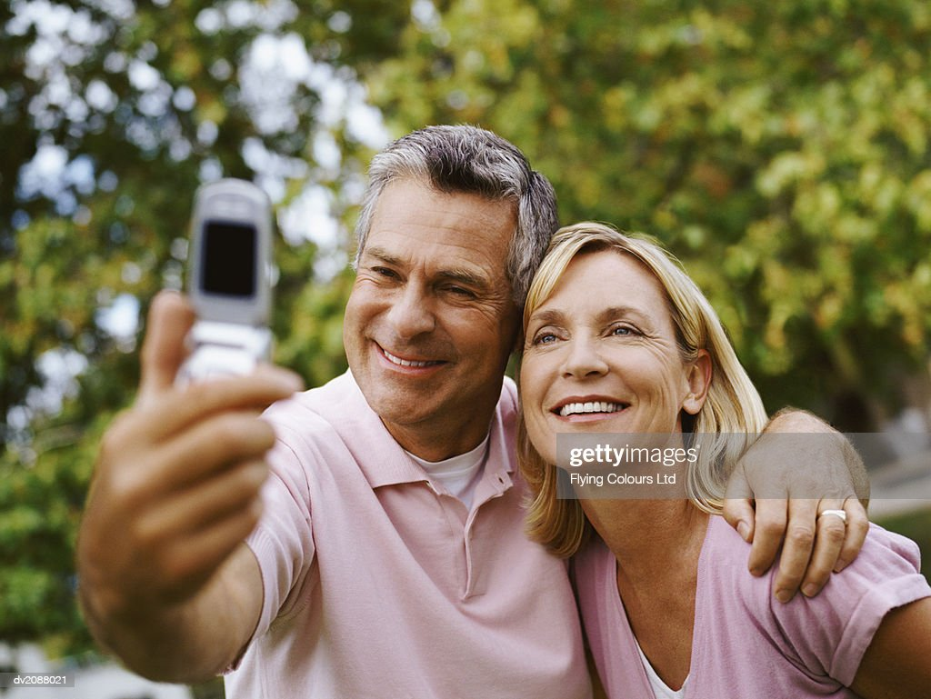 Mature Couple Photographing Themselves With a Mobile Phone : Stock Photo