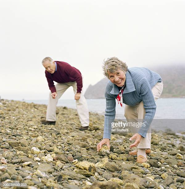 Mature couple picking rocks on beach