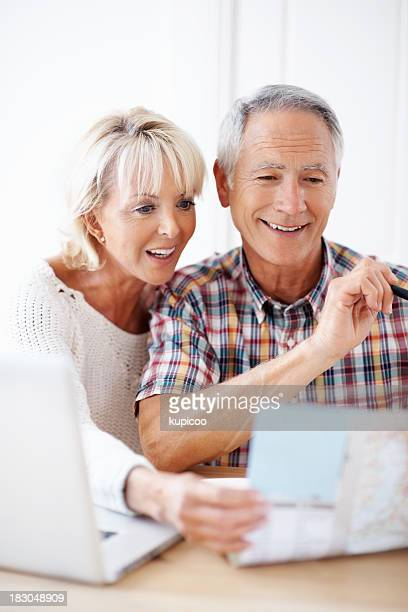 Mature couple planning their vacation with map and laptop