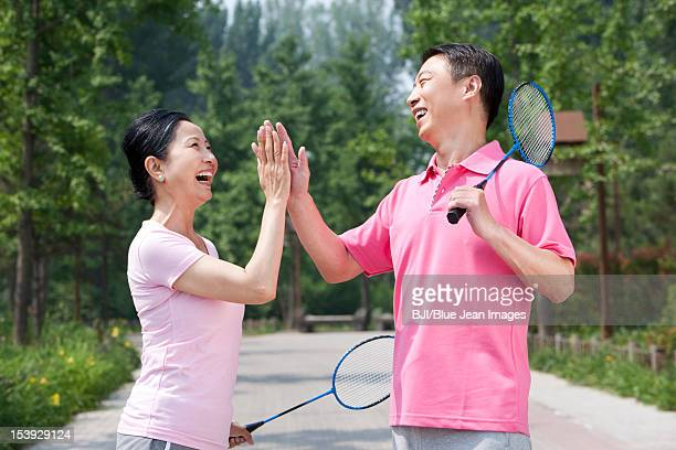mature couple playing badminton in park - badminton sport stock pictures, royalty-free photos & images