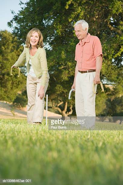 mature couple playing game of horseshoes - horseshoe stock pictures, royalty-free photos & images