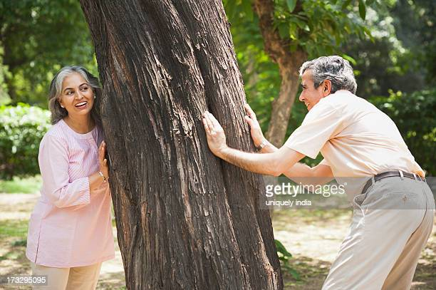 Mature couple playing hide and seek in a park, Lodi Gardens, New Delhi, India