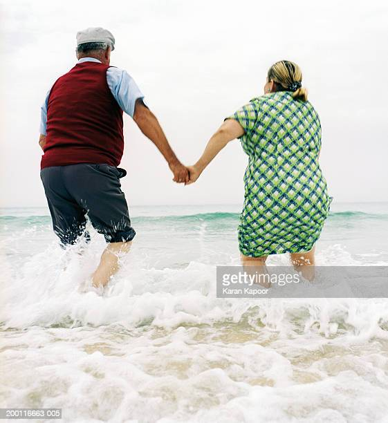 Mature couple playing in surf, rear view