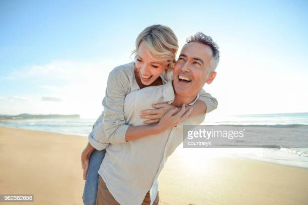 mature couple playing on the beach at sunset or sunrise. - donna 50 anni foto e immagini stock