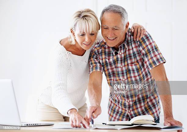 Mature couple pointing on map while planning their vacation