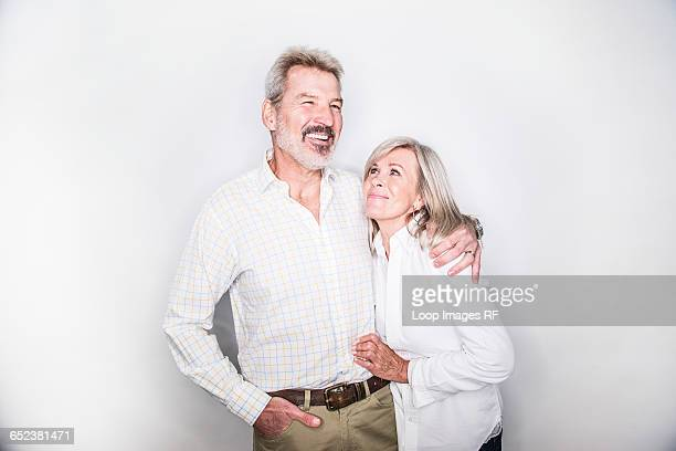 A mature couple posing in a studio looking happy