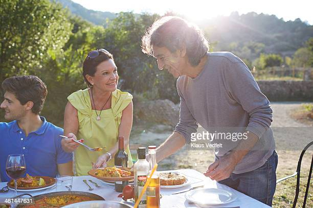 Mature couple pouring Paella on the plate