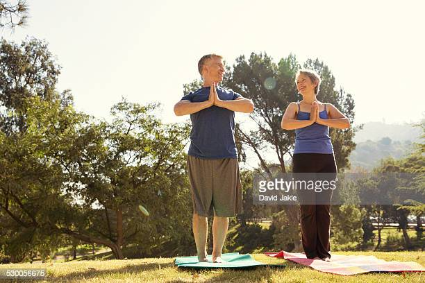Mature couple practicing yoga in park