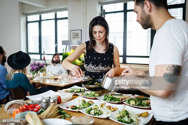 Mature couple preparing dishes for dinner party