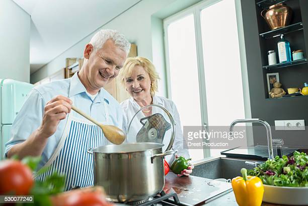 Mature couple preparing food, smiling