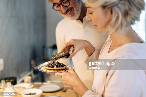 mature couple preparing pancakes in kitchen at home - 45 49 years stock pictures, royalty-free photos & images