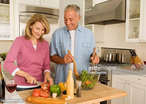 Mature couple preparing salad in kitchen
