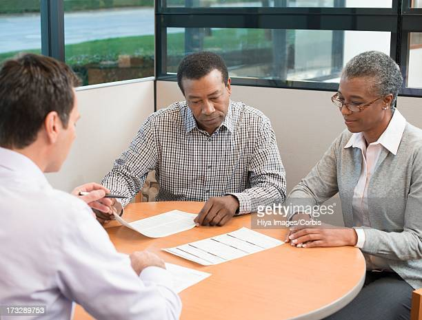 Mature couple preparing to sign loan contract