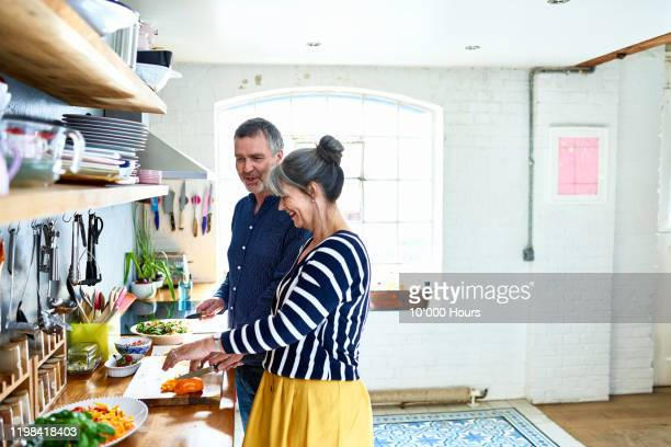 mature couple preparing vegetarian meal in stylish kitchen - healthy eating stock pictures, royalty-free photos & images