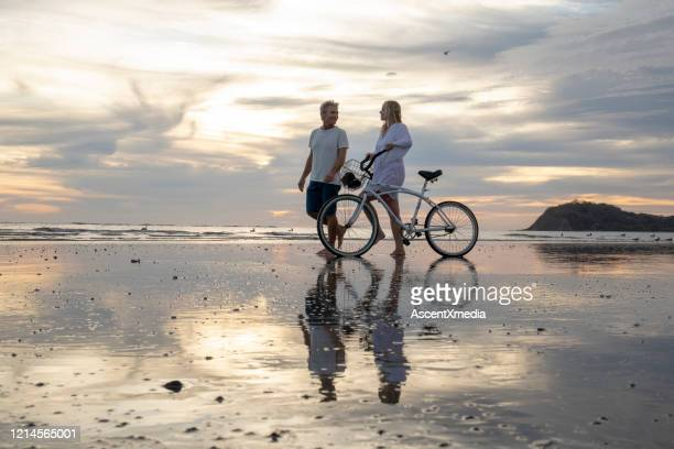 mature couple push bike down beach at sunrise - early retirement stock pictures, royalty-free photos & images