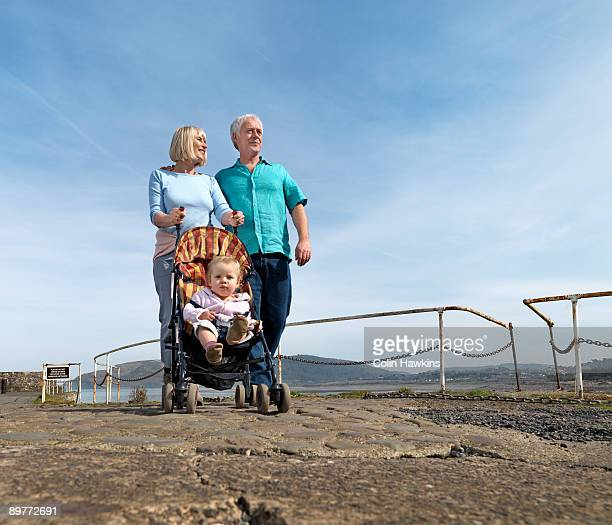 mature couple pushing child in buggy - ポーロック ストックフォトと画像