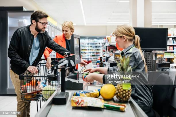 mature couple putting groceries on conveyor at checkout - cash register stock pictures, royalty-free photos & images