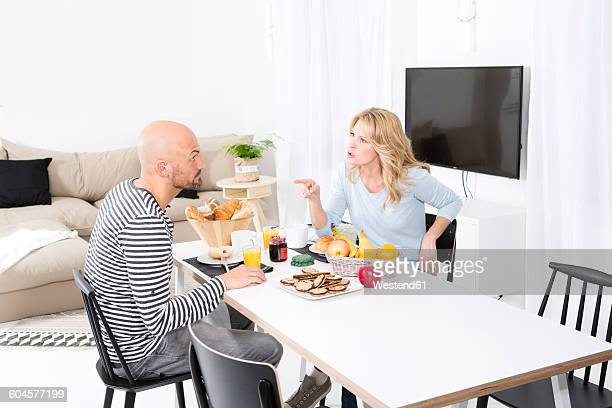 Mature couple quarreling at breakfast table