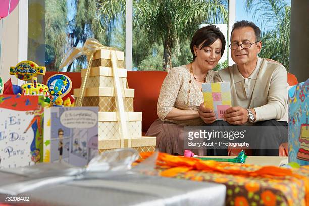 Mature couple reading birthday card in living room