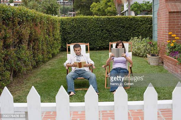 Mature couple reading in back yard of house