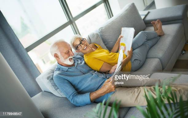 mature couple reading magazines and having a conversation. - wealth stock pictures, royalty-free photos & images