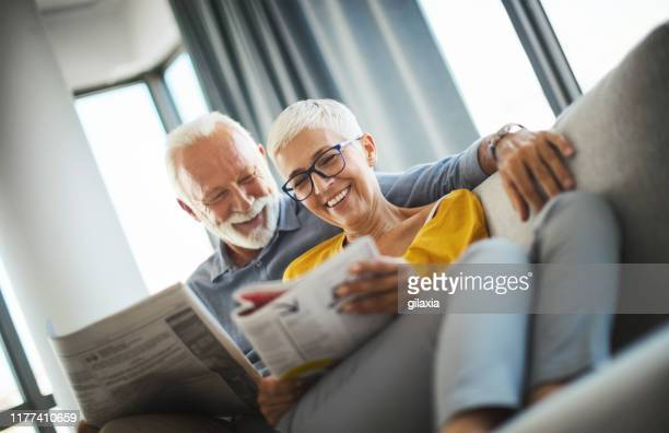 mature couple reading magazines together. - love magazine stock pictures, royalty-free photos & images