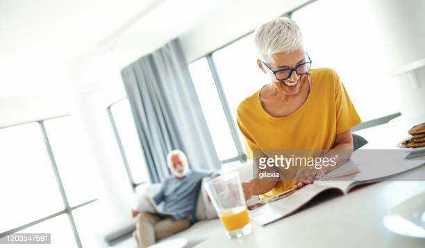 mature couple reading newspapers and having coffee. - magazine stock pictures, royalty-free photos & images