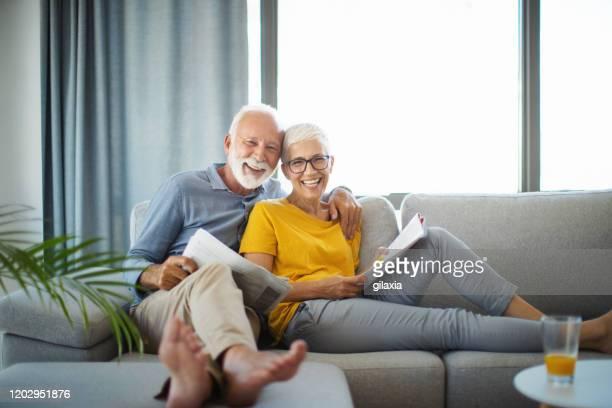 reifes paar liest zeitungen an einem wochenende nachmittag. - alter erwachsener stock-fotos und bilder