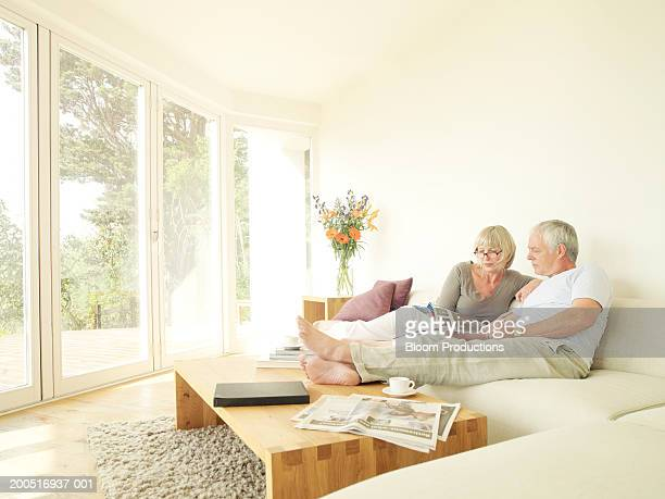 Mature couple reading on sofa