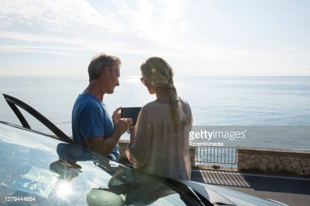 mature couple relax beside car door, look at digital tablet - early retirement stock pictures, royalty-free photos & images