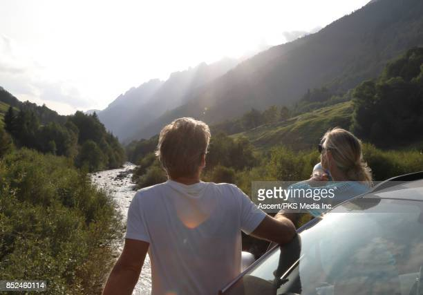 Mature couple relax beside car, looks off to mountains, river