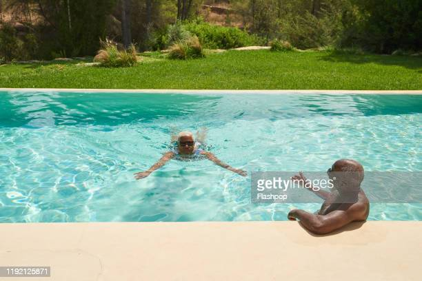 a mature couple relax in a pool together - poolside stock pictures, royalty-free photos & images