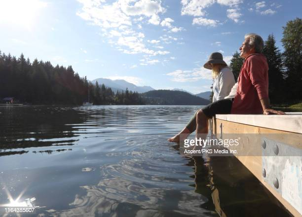 mature couple relax on a dock over a mountain lake - image stock pictures, royalty-free photos & images