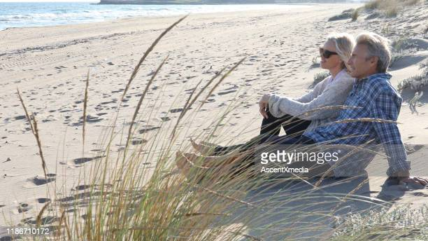mature couple relax on beach at sunrise - early retirement stock pictures, royalty-free photos & images