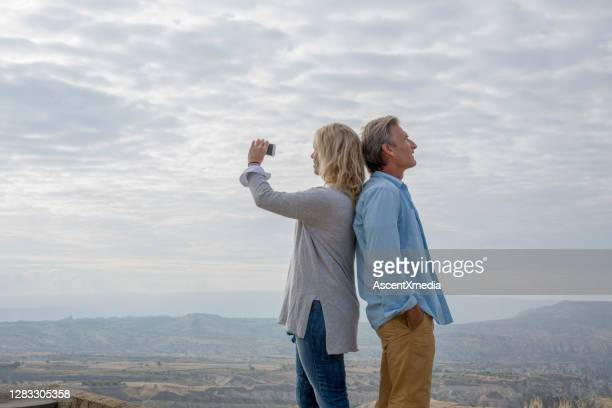 mature couple relax on elevated viewpoint in the morning - 50 59 years stock pictures, royalty-free photos & images