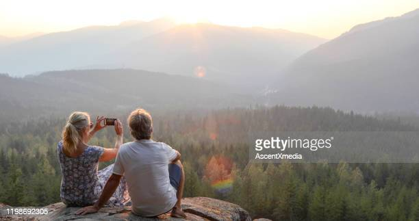 mature couple relax on mountain ledge, look out to view - canadian rockies stock pictures, royalty-free photos & images