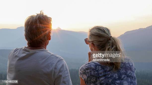 mature couple relax on mountain ridge at sunrise - look back at early colour photography stock pictures, royalty-free photos & images