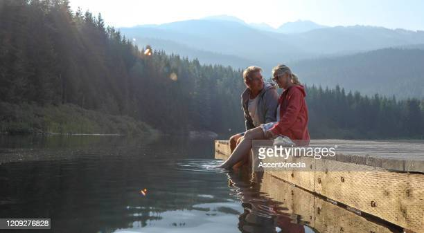 mature couple relax on wooden pier, looks out across lake - pier stock pictures, royalty-free photos & images