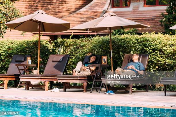 Mature couple relaxed by swimming pool in resort