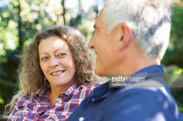 mature couple relaxing in their garden - richard drury stock pictures, royalty-free photos & images