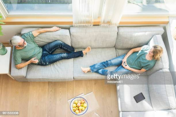 mature couple relaxing on couch at home - hygge stock pictures, royalty-free photos & images