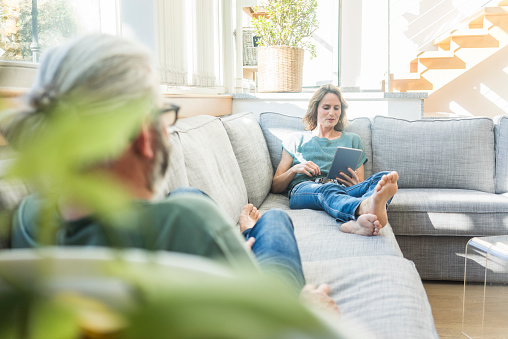 Mature couple relaxing on couch at home with woman holding tablet - gettyimageskorea