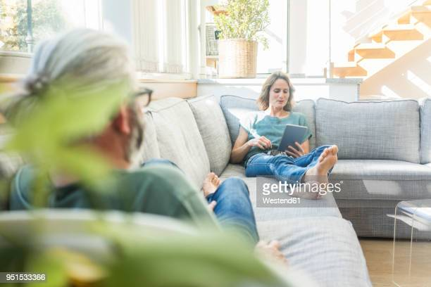 Mature couple relaxing on couch at home with woman holding tablet