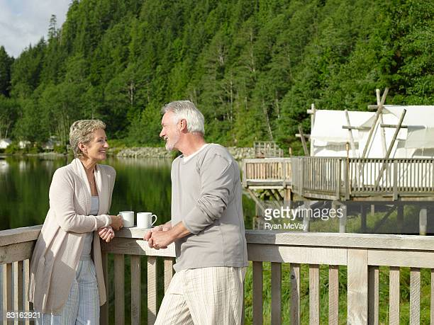 Mature couple relaxing on deck outside tent.