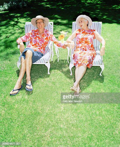 Mature couple relaxing on garden chairs, holding hands, smiling